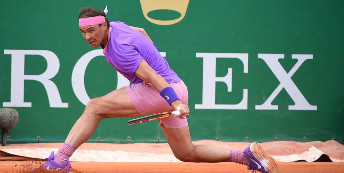 Rafa Nadal slides into a backhand return on red clay